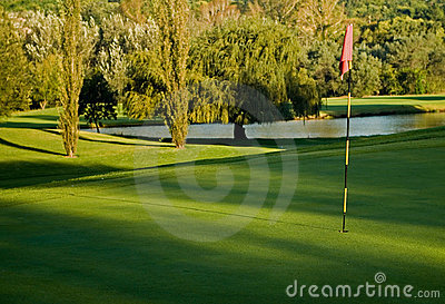 Golf green, flag and water hazard