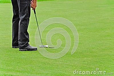 Golf, in Loch die Kugel einsetzend