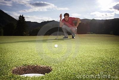 Golf player analyzing green.