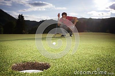 Golf player analyzing green.