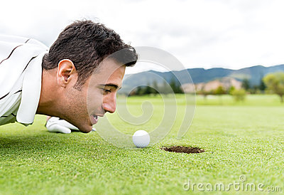 Golf player blowing the ball