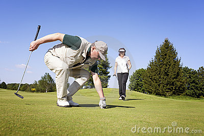 Golf player couple on green picking ball.