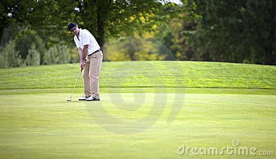 Golf player putting on green