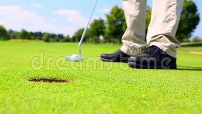 A golf player putting. Low angle view on feet only stock video footage
