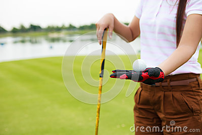 Golf player showing golf ball holding golf club
