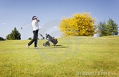 Golf player swinging club on fairway.