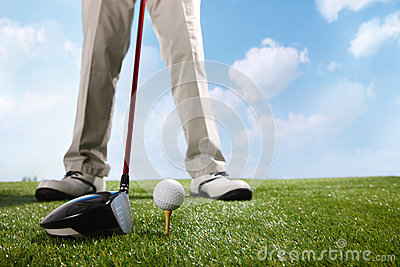 Golf player teeing up to hit ball