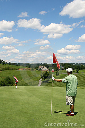 Golf - Son Putting Ball at Father Tending Flag