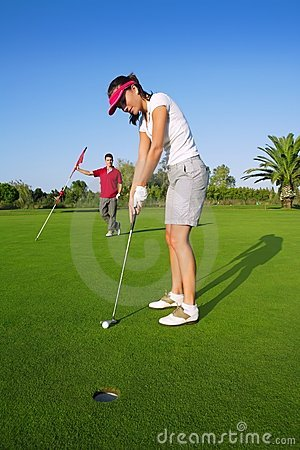Golf woman player green putting hole golf ball