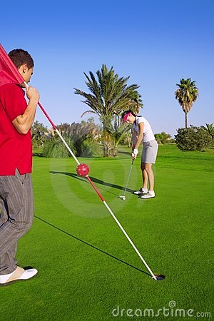 Golf woman putting gol ball and man holds flag