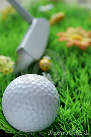 Golfball and club on artificial grass