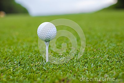 Golfball on a tee against the golf course