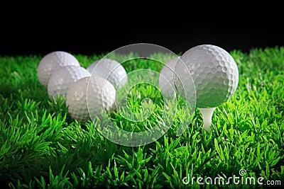 Golfboll och utslagsplats i grönt gräs
