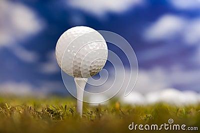 Golfboll på grönt gräs över en blå sky