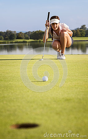Golfer analyzing green for putting ball into cup.