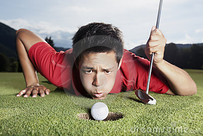 Golfer blowing ball into cup.