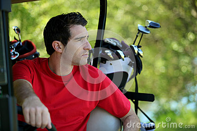 Golfer in buggy.
