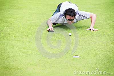 Golfer checking line of putt