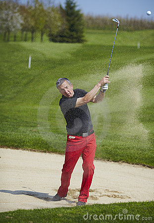 Golfer hitting a ball in the bunker