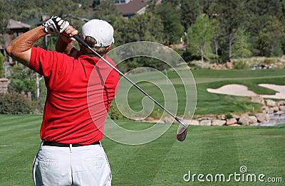 Golfer hitting ball on green