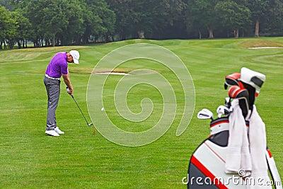 Golfer iron shot on a par 4 fairway.