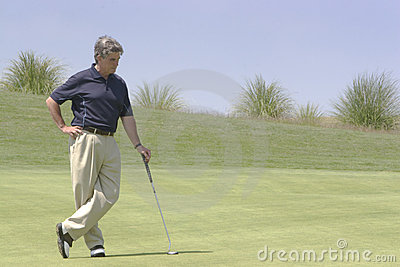 Golfer leaning against putter