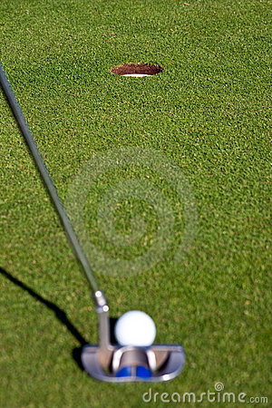 Golfer lining up a short putt - focus on the hole