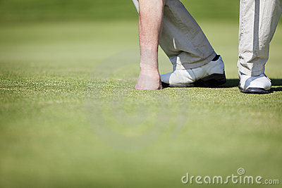 Golfer picking up ball.