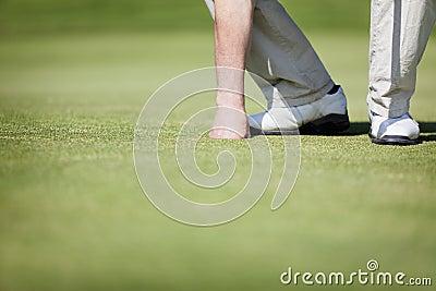 Golfer picking up ball.