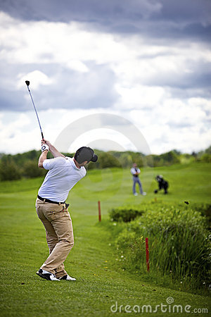 Golfer pitching over obstacle