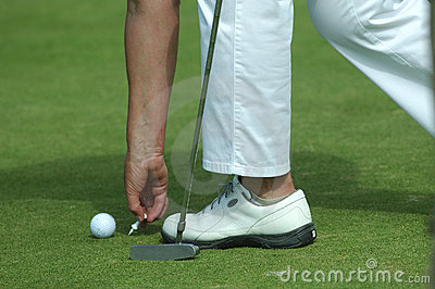 Golfer placing golf ball on a tee