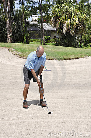 Golfer putting from a sand trap