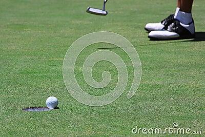 Golfer sinking a long putt