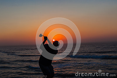 Golfer Swinging Sunrise Ocean