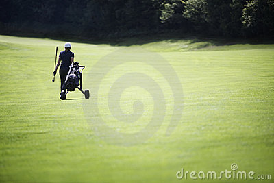 Golfer walking on fairway with bag.