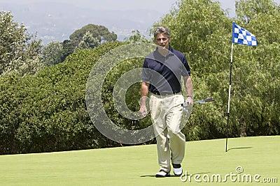 Golfer walking off green
