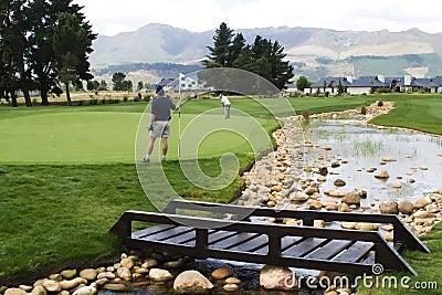 Golfers on green with bridge