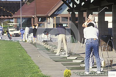 Golfers lined up on putting range, Editorial Image