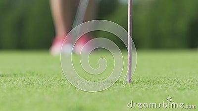 Golfspieler, der Golfball setzt, um zu durchlöchern Der Spieler, der im Golfplatz auf Sonnenuntergang spielt, ist schöne Natur Üb stock footage