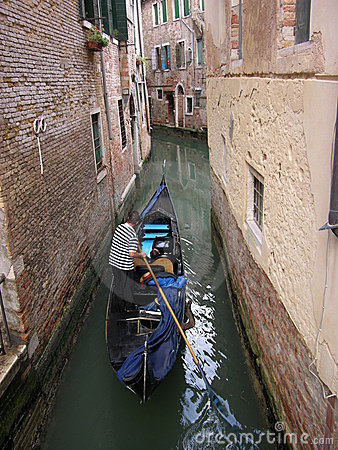 Gondola in a narrow canal of Venice