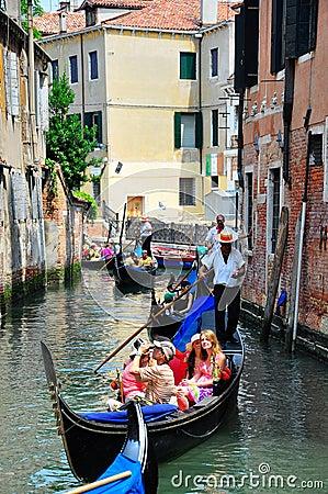 Gondolier navigating a gondola through canal Editorial Photography