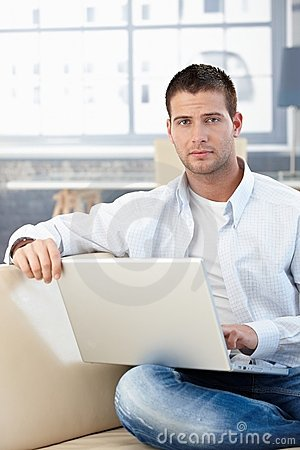 Goodlooking man working at home on laptop