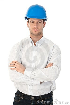 Goodlooking young architect standing arms crossed