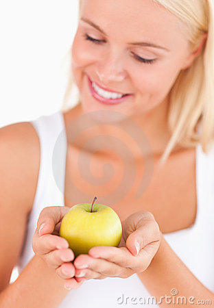 Gorgeous blond woman holding an apple