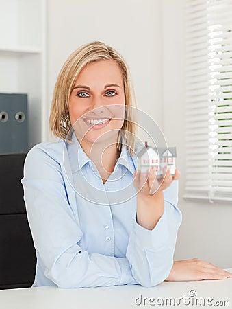 Gorgeous blonde businesswoman showing miniature