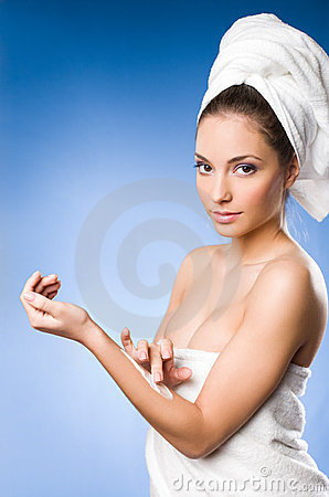 Gorgeous brunette spa  woman using moisturizer.