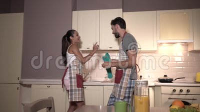 Gorgeous couple is dancing and working at the same time. Girl gives guy glasses. He is drying them up. Also they are. Singing during dance. Girl is laughing and stock footage