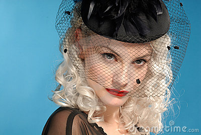 Gorgeous retro girl in forties hat with feathers