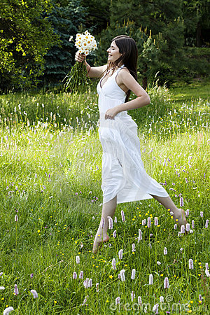Gorgeous teenage girl jumping in a flowery meadow