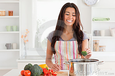 Gorgeous woman preparing vegetables while standingg